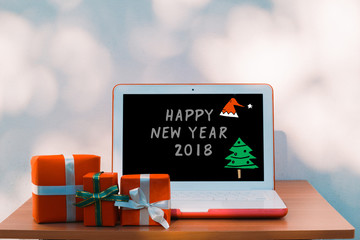 Christmas Holiday and online Shopping concept- new year, presents box and laptop computer with E-mails on wooden table over bokeh wall background and copy text space for writing messages