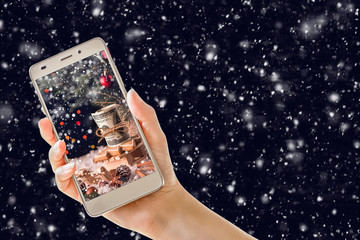 hand holding mobile phone with christmas screen