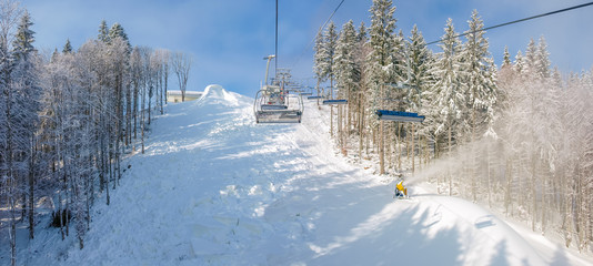 Chairlift and ski piste during preparation in forest