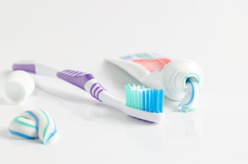 A tube of toothpaste and a toothbrush on white background