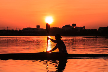 Rowing kayak in sunset