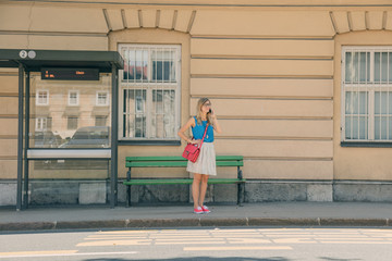 Cute girl talking on the phone and waiting for a bus in the city.