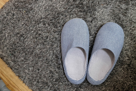 Slippers on the Gray carpet, top view with space for text