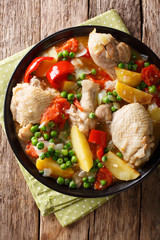 Pieces of chicken stew with potatoes, peppers, tomatoes, peas and onions close-up. Vertical top view