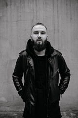 Modern young bearded man in black style clothes standing in urban background.