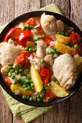 Filipino Afritada: slices of chicken with vegetables close-up in a bowl. Vertical top view