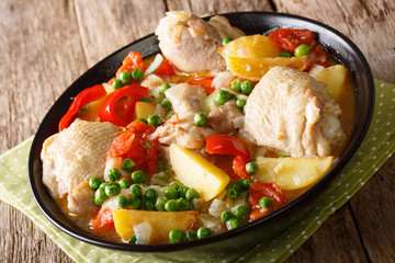 Pieces of chicken stew with potatoes, peppers, tomatoes, peas and onions close-up. horizontal