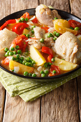 Philippine Afritada: chicken stew with vegetables close-up in a bowl. vertical
