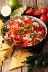 Mexican pico de gallo close-up in a bowl and nachos. vertical