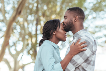Romantic young African man kissing his girlfriend's forehead outdoors