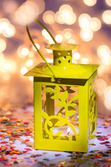 Yellow lantern om a wooden table, bokeh on a background