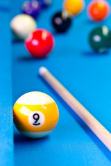 Billiard pool game nine ball with cue on billiard table