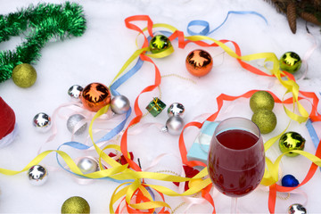 Two glasses of wine and gifts with a red satin ribbon, apples , pine cones, branches, gold ornaments garlands