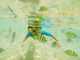 Kid in swimming suit snorkeling in the Indian Ocean