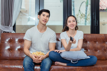 Couple together watching television funny reaction on sofa in living room at room