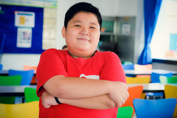 Asian obese boy standing crossed arms and cute smile