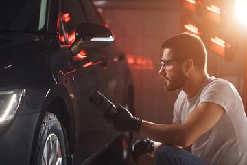 man checks the polishing with a torch