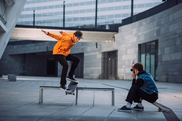 man taking photo of skateboarder jumping over bench in urban location