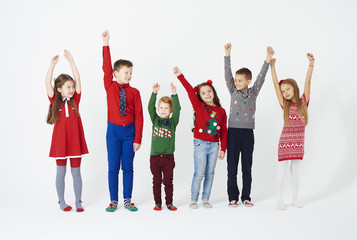 Front view of children hands up standing in a row