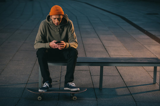 skateboarder sitting on bench and using smartphone