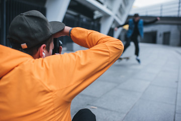 close-up shot of man taking photo of skateboarder doing trick