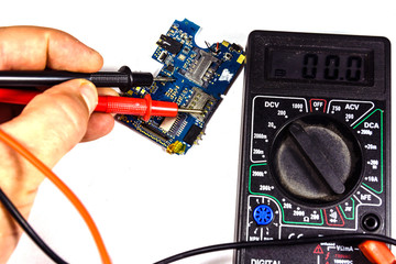 Inspecting of the electronic circuit board with multimeter. White background
