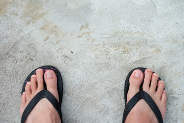 Feet of men wearing black sandals on the cement floor