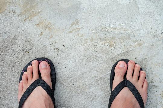 Feet of men wearing black sandals on the cement floor