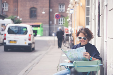 Young beautiful female traveler sits in cafe on the street and looking at the map