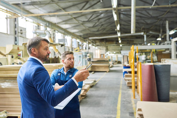 Side view portrait of handsome mature businessman touring modern factory inspecting quality of production, assisted with young workman, copy space