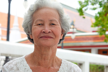 Older Asian women with grayish hair have smiling faces onTemple background