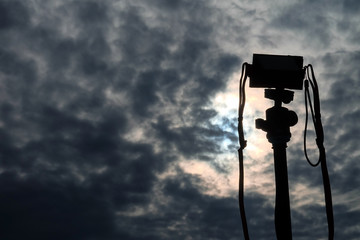 Silhouette Camera  on the tripod on the morning sky background