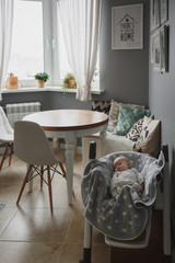 Newborn child sleeping in a child seat in a cozy grey kitchen. The atmosphere of coziness and silence.