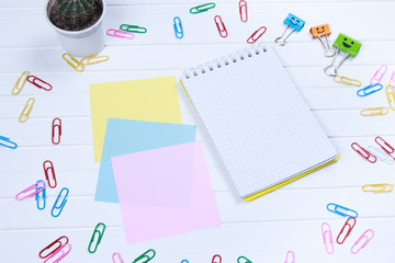 note paper and note book with paper clips on white wooden background