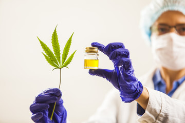 Woman doctor holding a cannabis leaf and oil