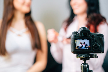 Young female blogger on camera screen doing makeup from client