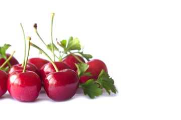 Fresh red cherries lay on white isolated background in side view with copy space. Cherry have high vitamin C and have sweet and sour taste. Healthy and delicious fruit concept.