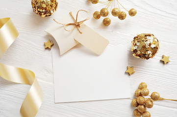 Mockup Christmas greeting card top view and gold ball, flatlay on a white wooden background with a ribbon, with place for your text