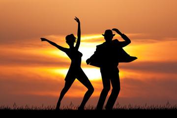 man and woman dancing tango at sunset