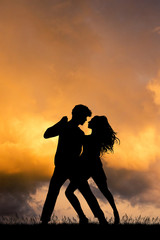 man and woman  dancing at sunset