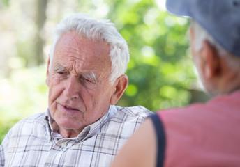 Two senior men talking in park