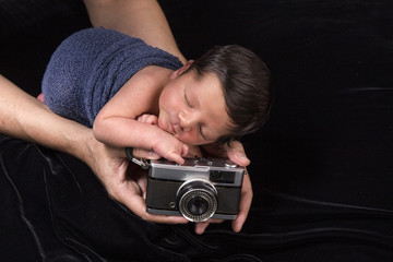 Newborn sleeping baby with old camera