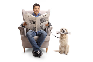 Young man seated in an armchair holding a newspaper and a labrador retriever with a newspaper