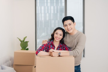 Young asian couple moving to a new apartment together.
