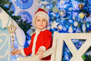 boy in a Santa suit standingnear to a Christmas tree