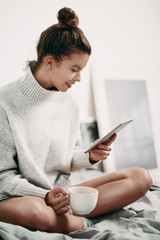 Girl sitting on bed in morning and using tablet