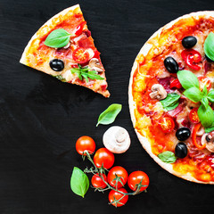 Hot pizza with Mozzarella cheese and tomatoes,  served om a black slate table board