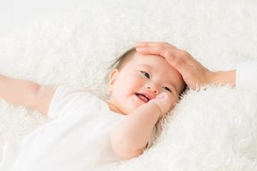 女性に撫でられる赤ちゃん(笑顔)