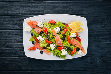 Salmon salad, feta cheese, salad leaves and fresh vegetables on the plate. On a wooden background. Top view. Free space for text.