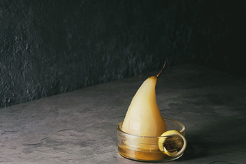 Traditional dessert poached pear in white wine served in glass bowl with syrup and lemon zest over gray texture table.